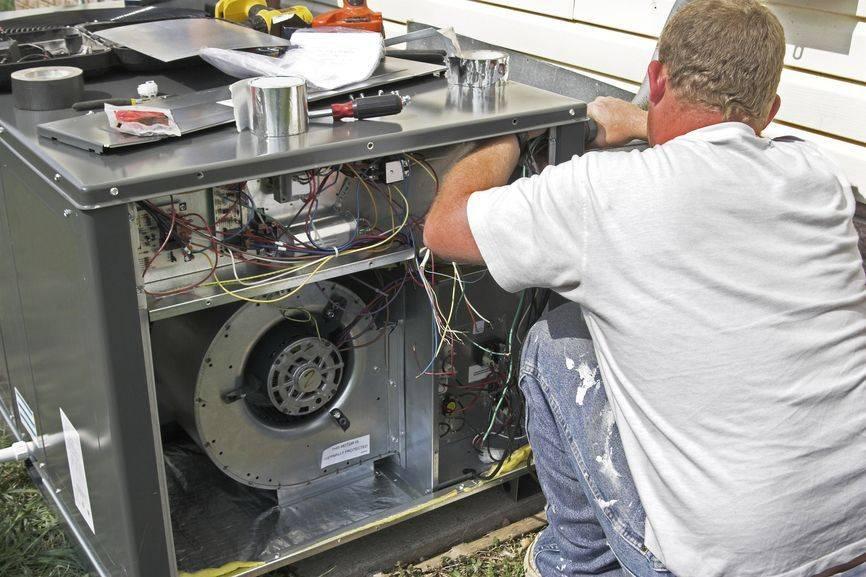 Air conditioner technician installing white AC unit